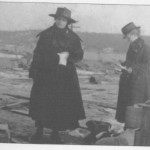 Women examining their insurance papers in front of the rubble